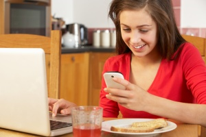 Teenage Girl Using Laptop And Mobile Phone Whilst Eating Breakfast